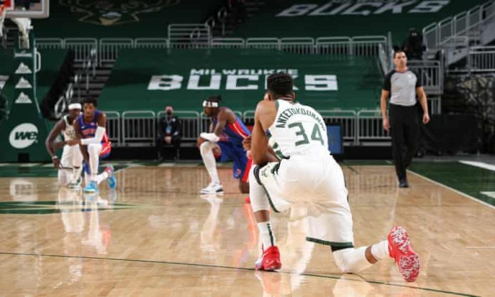 NBA players kneel down during their match.